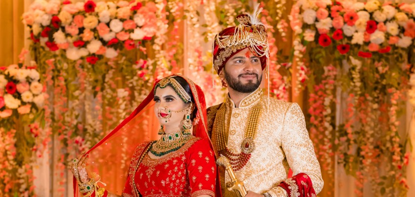 Happy couple in traditional indian outfits at their wedding