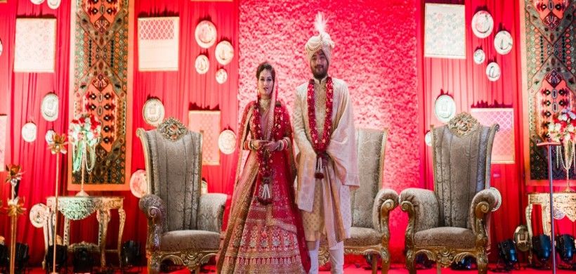 couple in traditional red outfits at their wedding