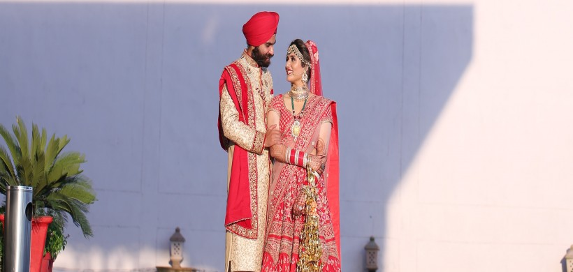 Punjabi couple in coordinated red outfits