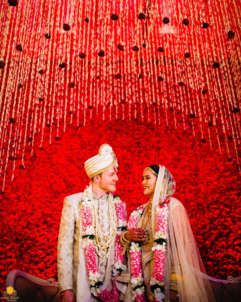 Bride and Groom on Wedding Stage with an All Red Roses Backdrop