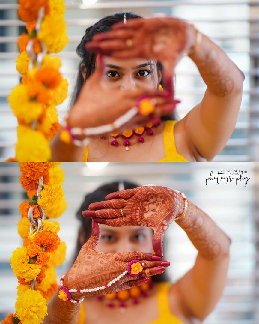 Bride Posing with Mehendi Hands in Haldi Ceremony with Marigold Decor