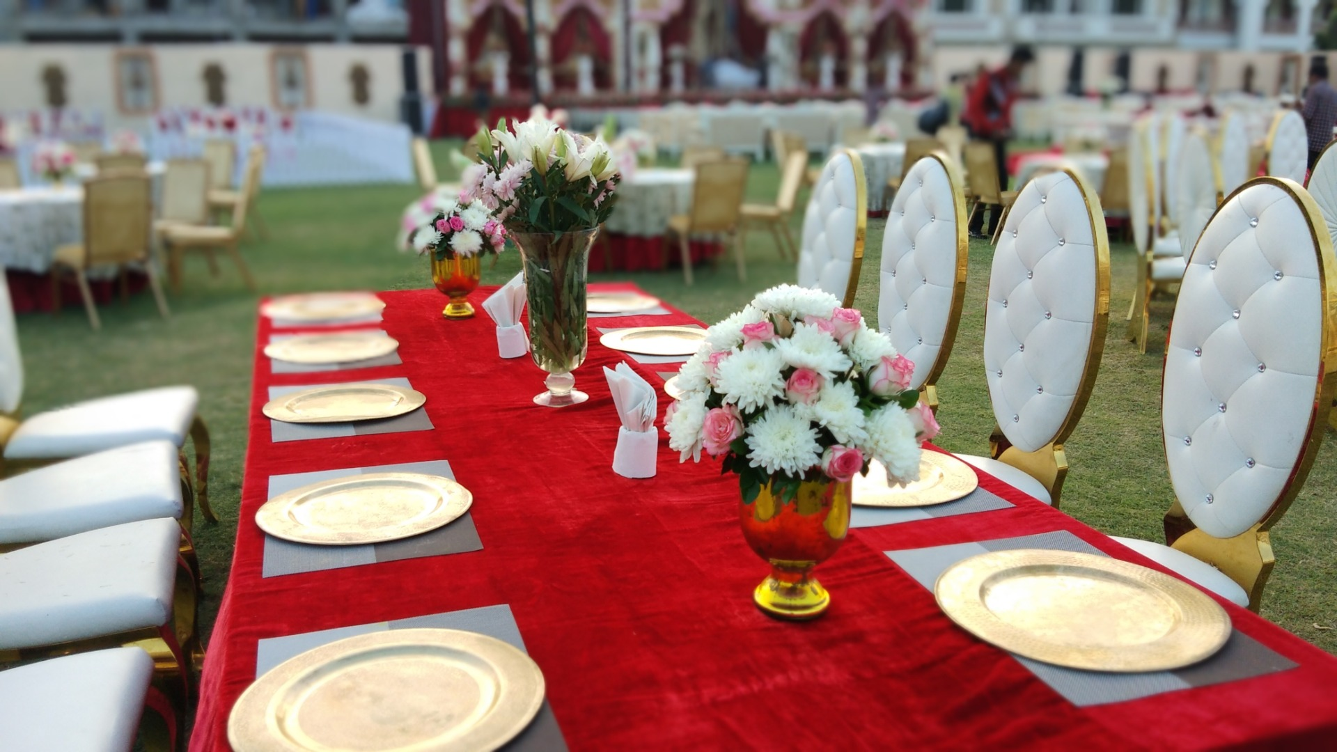 table set with golden plates and flowers as centerpiece
