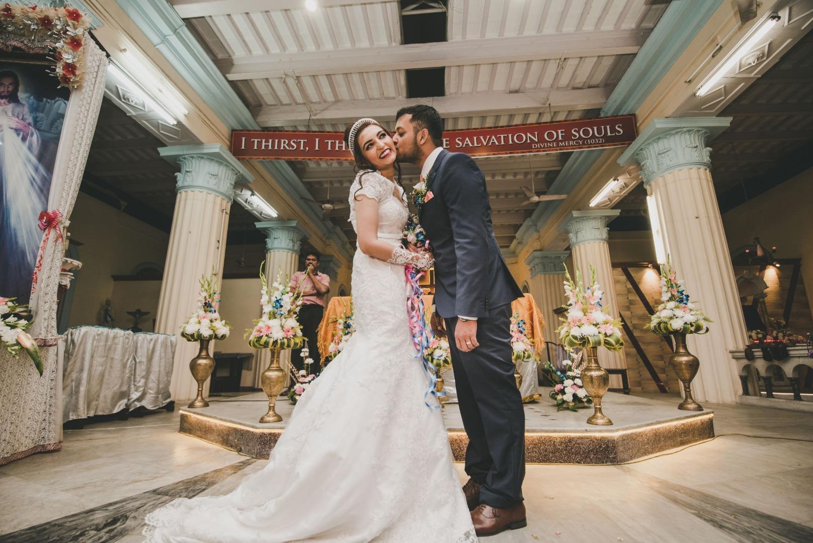 groom kissing on the bride's cheeks