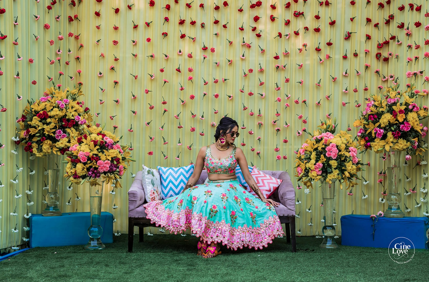 A Bride dressed in Turquoise & Pink with an Ombre Floral Mehendi Backdrop