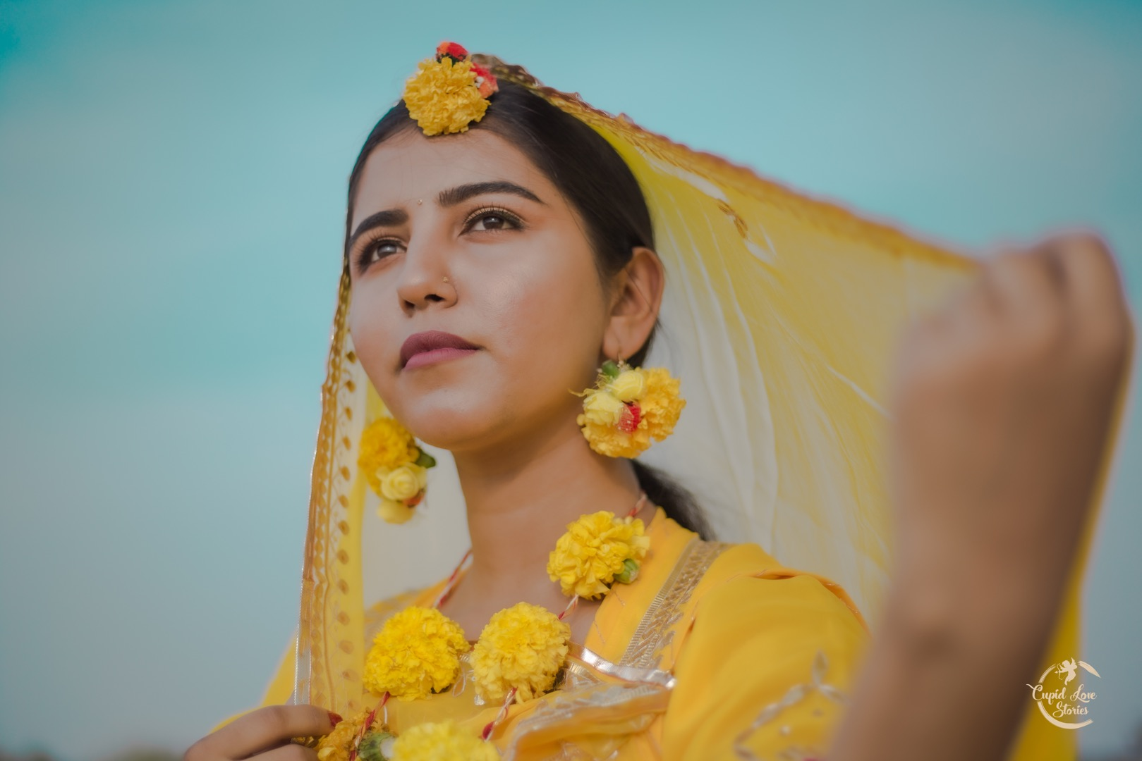 Beautiful bride in yellow attire for Haldi wearing floral jewelry