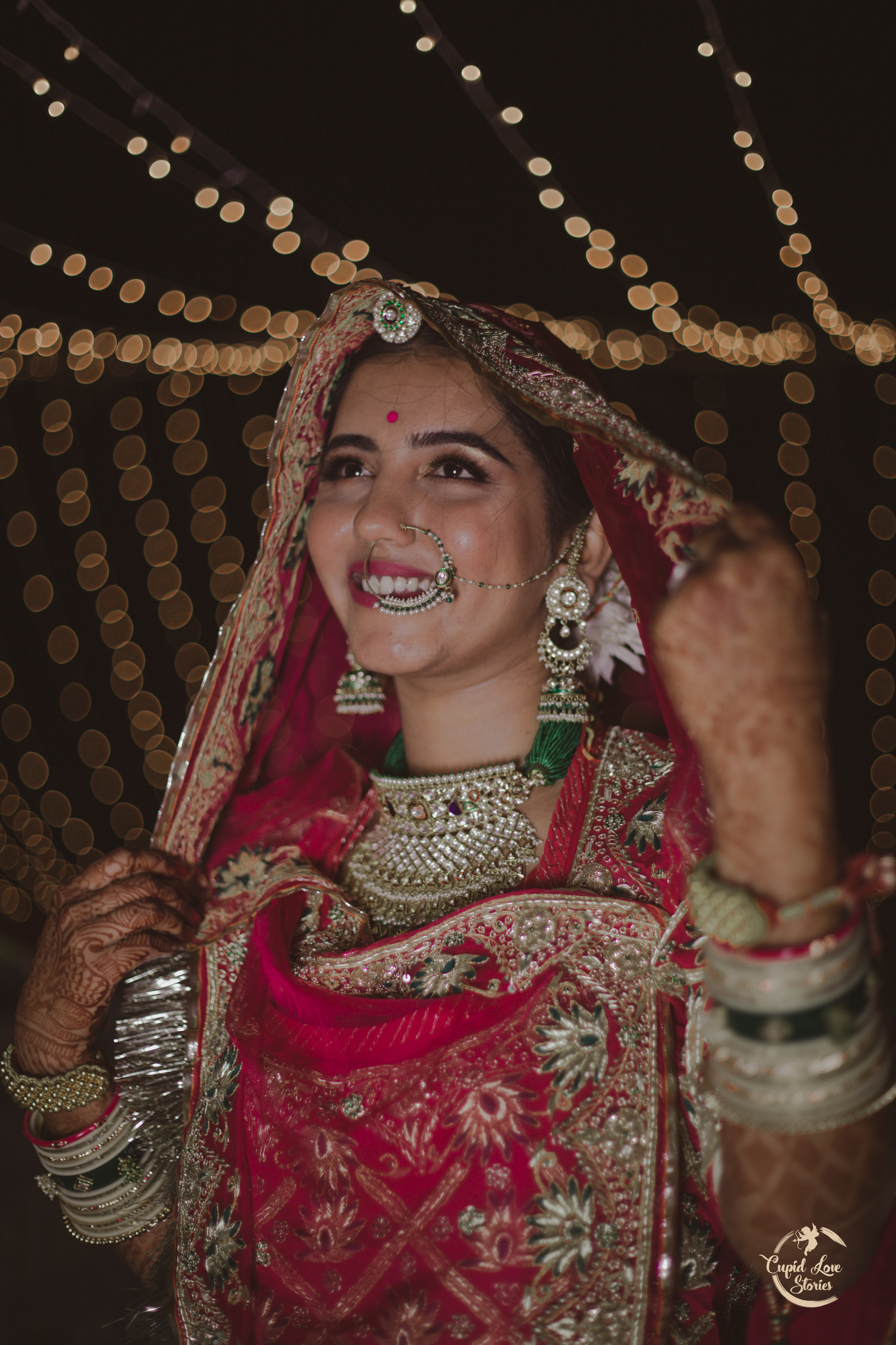 Traditional Indian bride under the lights wearing a beautiful maang-tikka