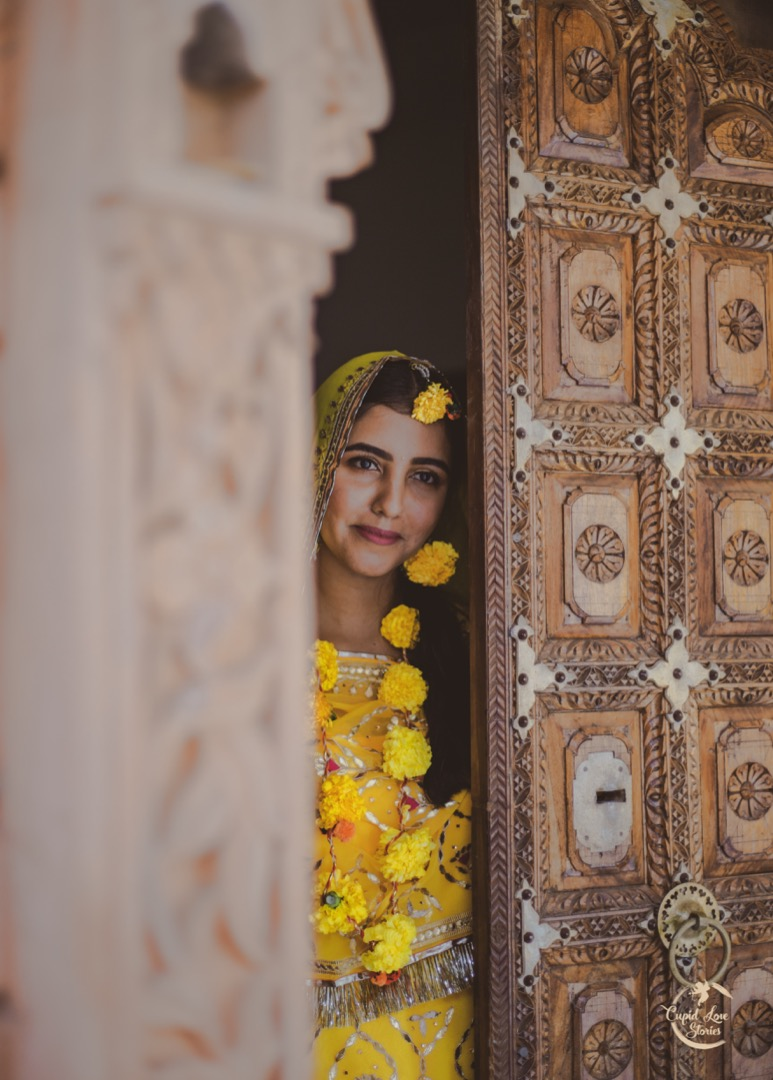 Smiling Bride Candid Picture in Yellow Outfit and Floral Jewellery for Haldi Ceremony