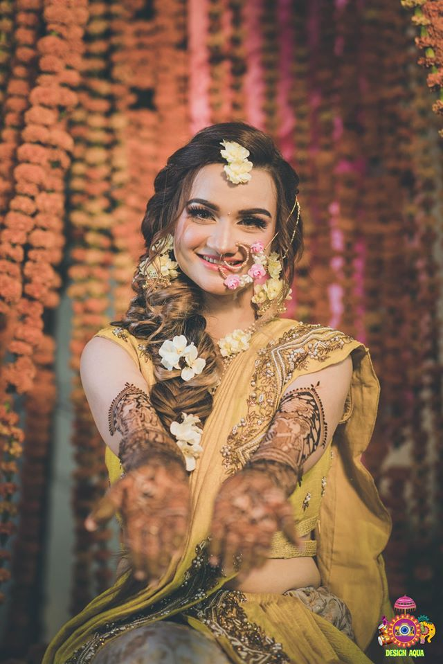 Bride in Yellow Outfit & White Floral Jewelry with Mehendi Hands Picture