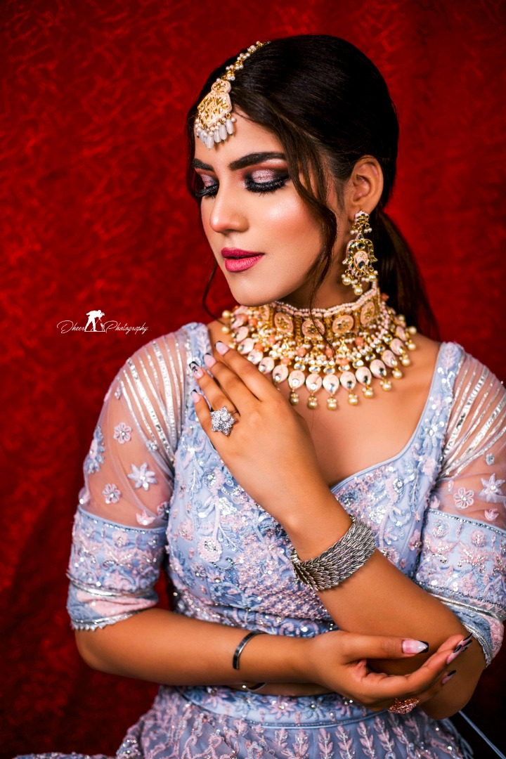 bride in pastel blue outfit and stunning bridal makeup