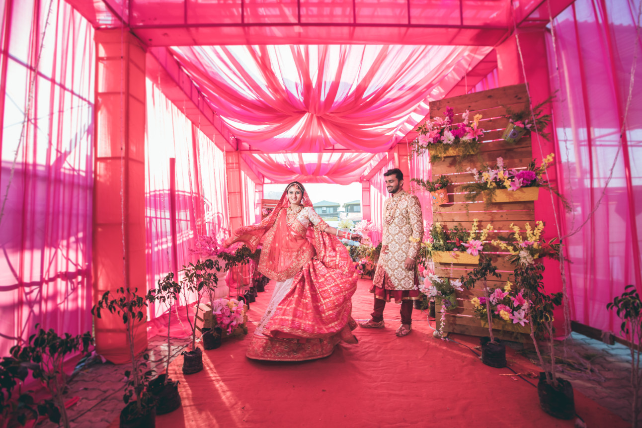 Twirling Bride and Groom in Pink Theme Drapes & Flowers Decor