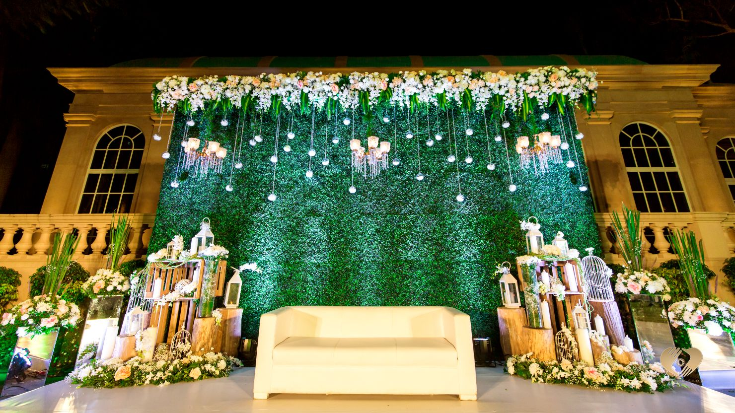 Floral Wedding Stage Decor with Green Wall Backdrop & Chandeliers