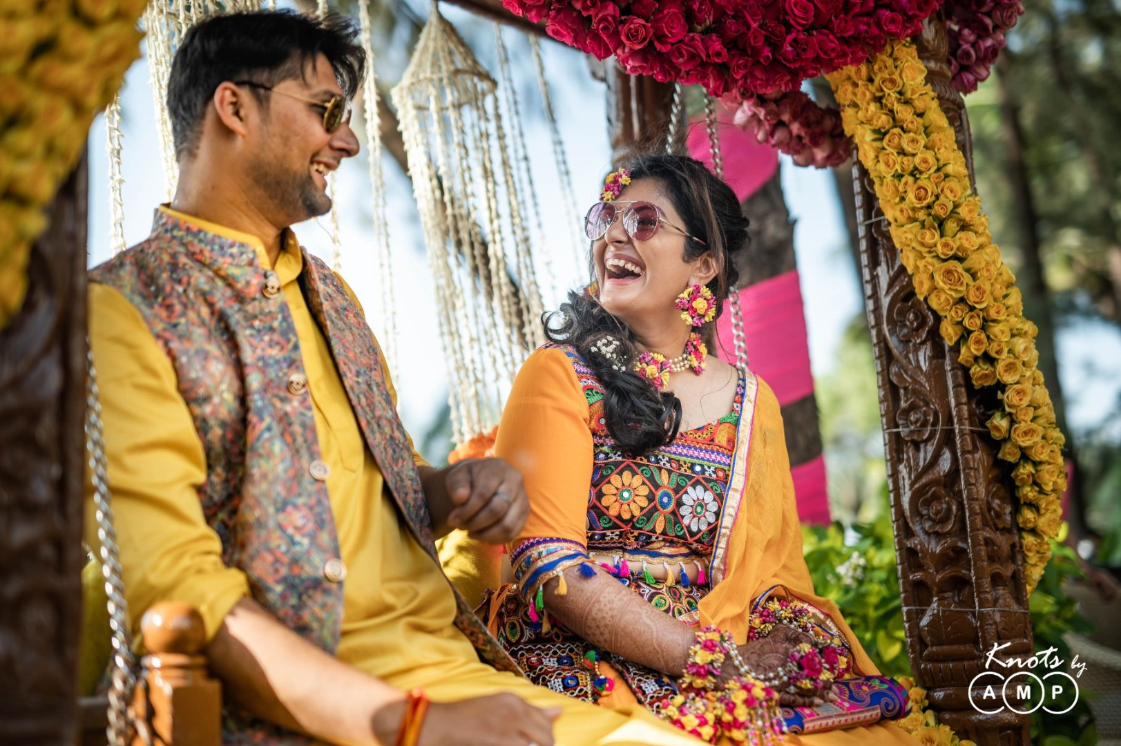 Laughing Bride & Groom for Haldi Ceremony on a Floral Decorated Swing Seating