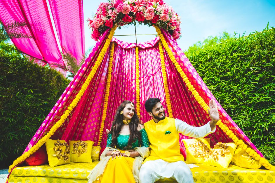 Bride & Groom Haldi Ceremony Picture in a Floral Decorated Seating Setup