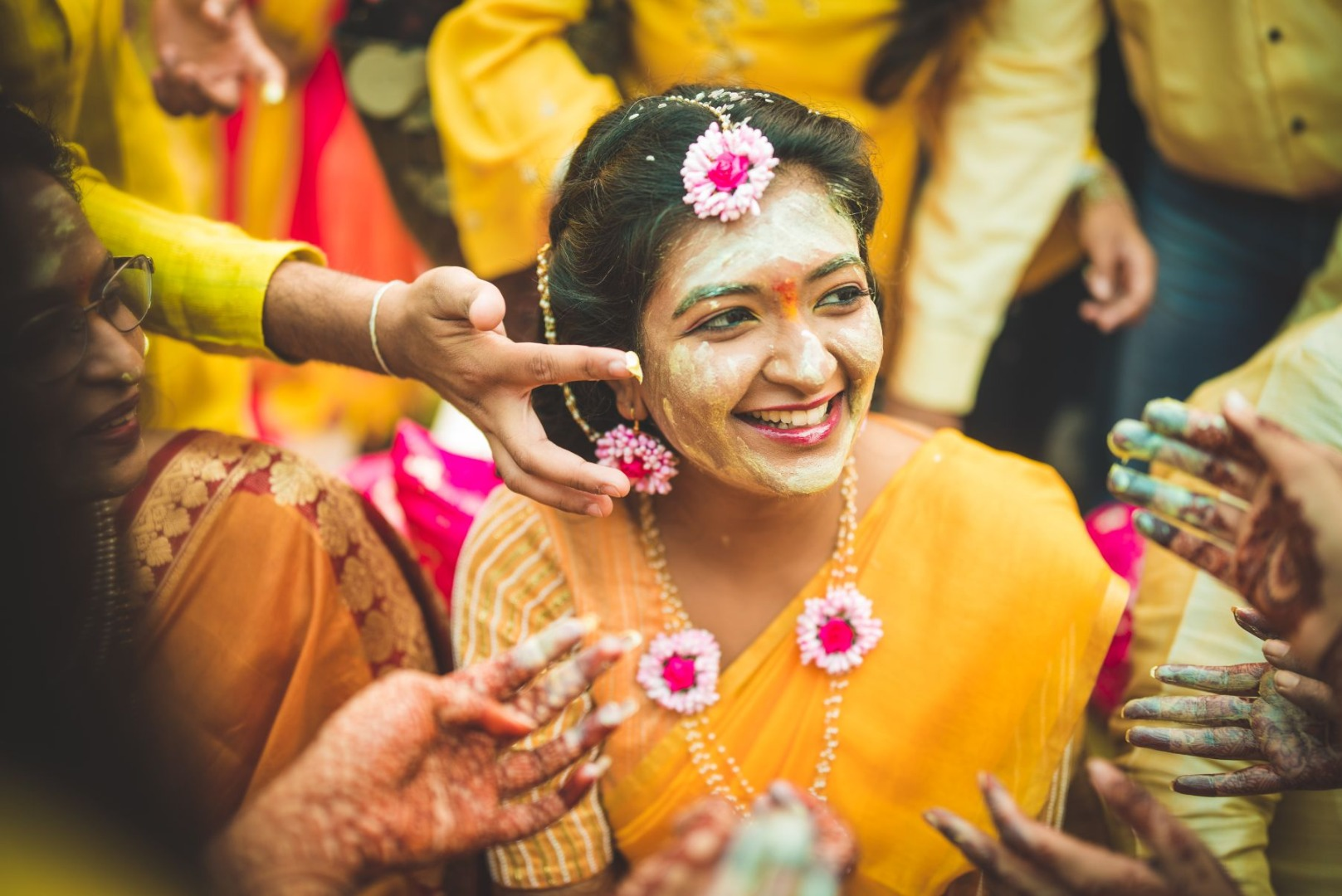 Bride During Haldi Ceremony in Yellow Outfit and Pink Floral Jewellery