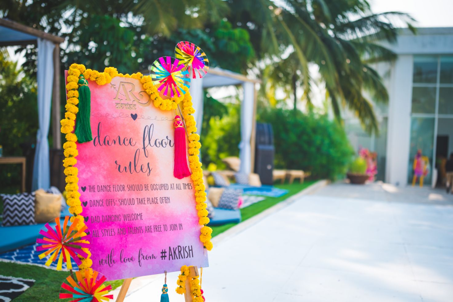 Sangeet Ceremony Welcome Signage Decorated with Marigolds and Pinwheels