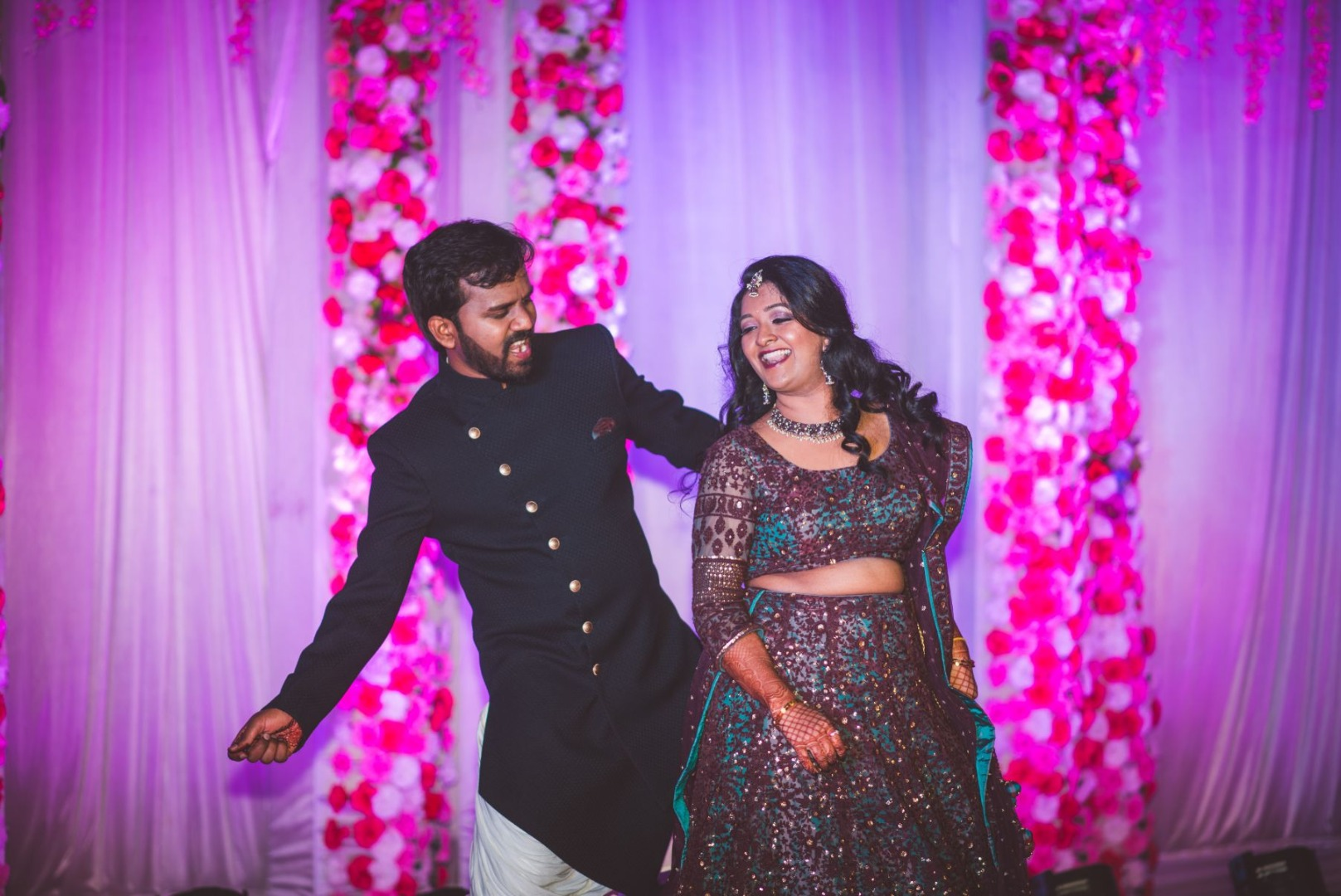 Dancing Bride & Groom in Coordinated Outfits and Pink Theme Floral Stage Decor