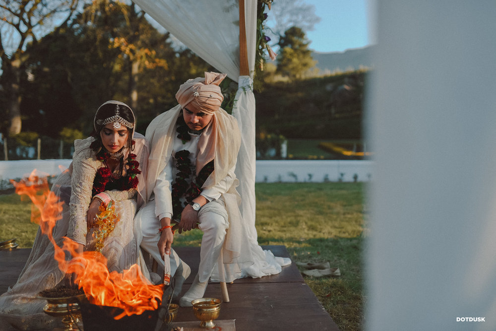 Bride & Groom During Indian Wedding Ritual in White Coordinated Wedding Outfits