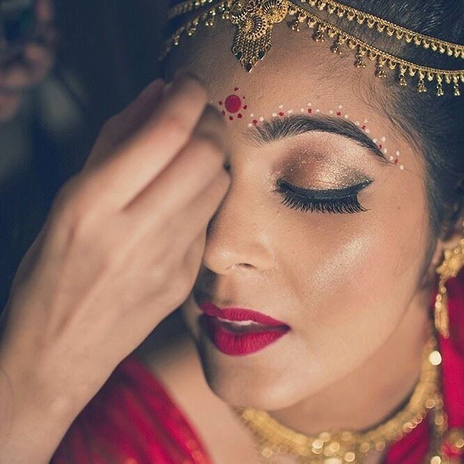 bengali bride in gold eye makeup with bold red lip