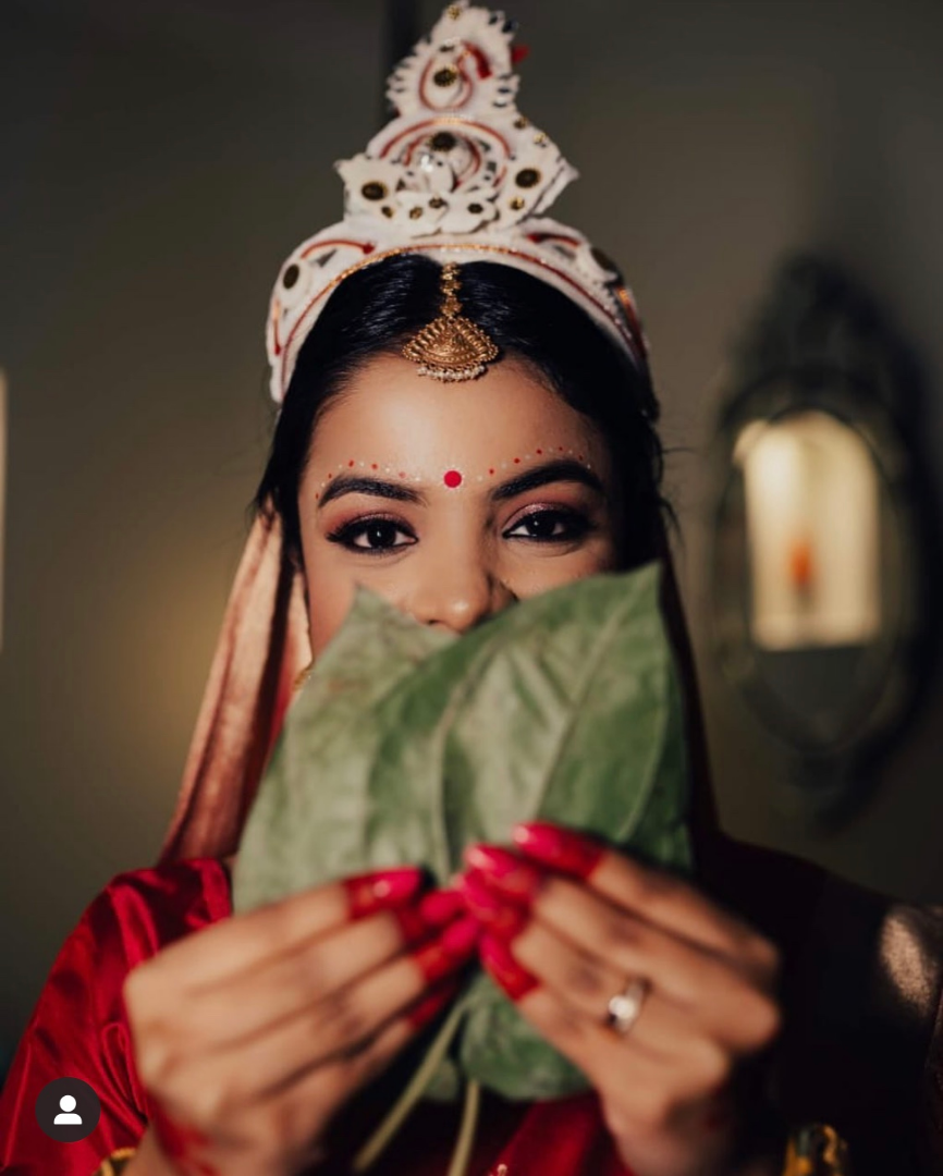 bengali bride poses with paan leaves