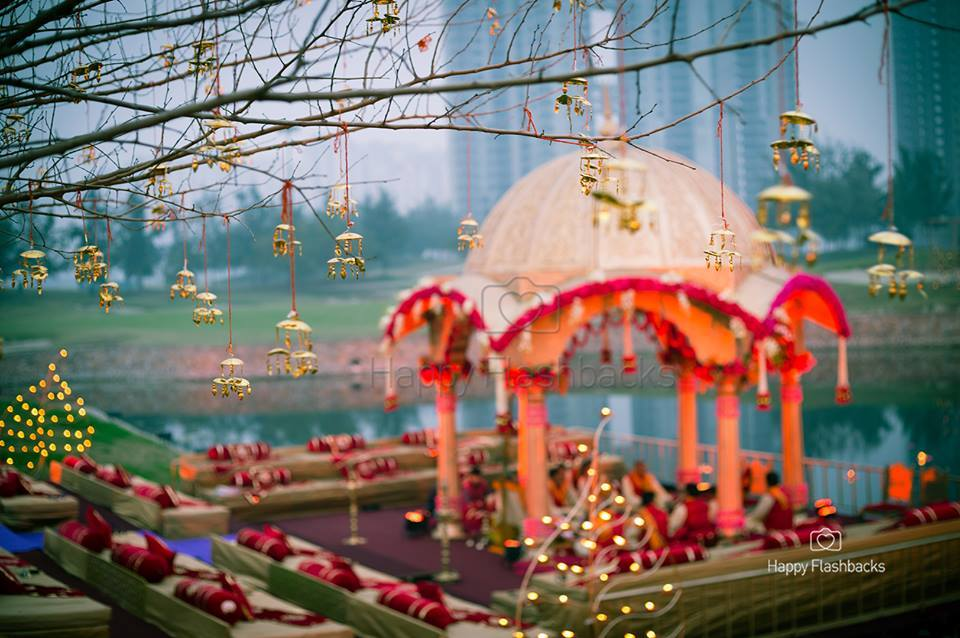 A Beautiful Mandap Decorated with Red Flowers on Water and Hanging Kaleeras Decor