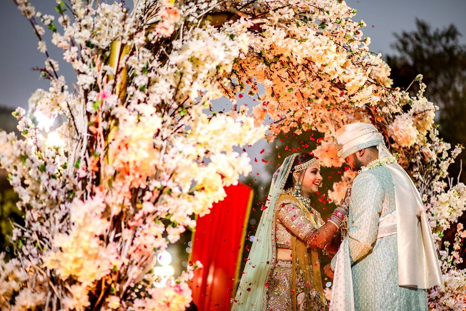 Bride & Groom Varmala Moment with Grand Floral Stage Decor