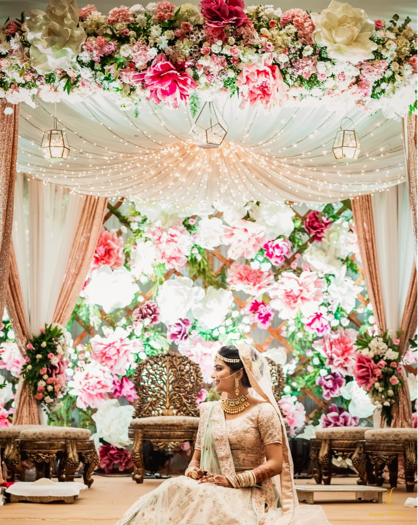 bride poses in front of her floral mandap