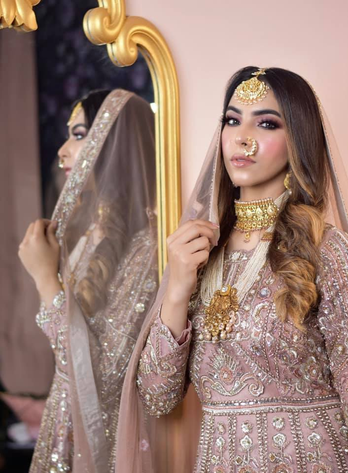 bride in pastel outfit posing in front of a mirror