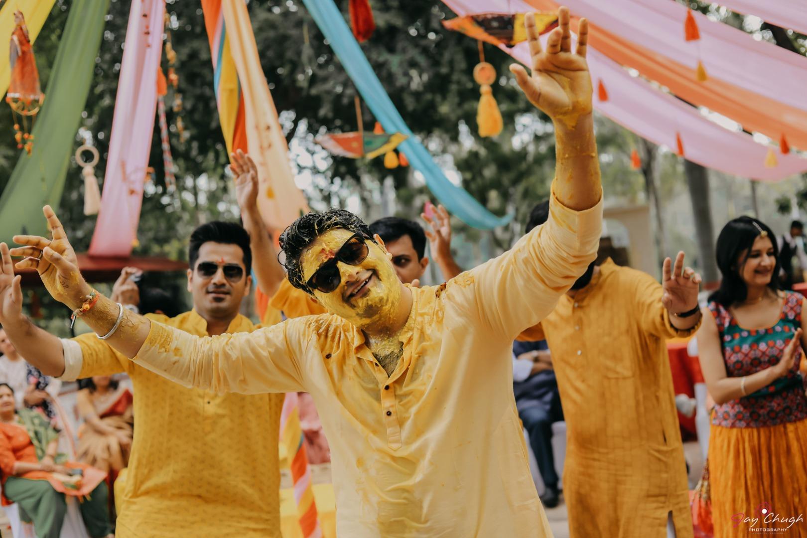 groom in yellow dancing at his haldi