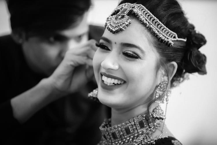 Black & White Picture of Smiling Bride Getting Ready For Wedding