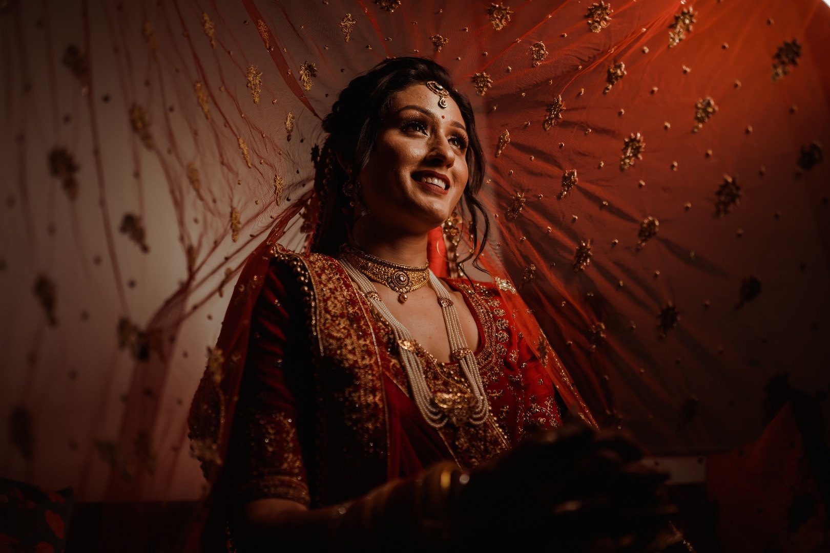 Beautiful capture of the bride in orange lehenga through the ghungat