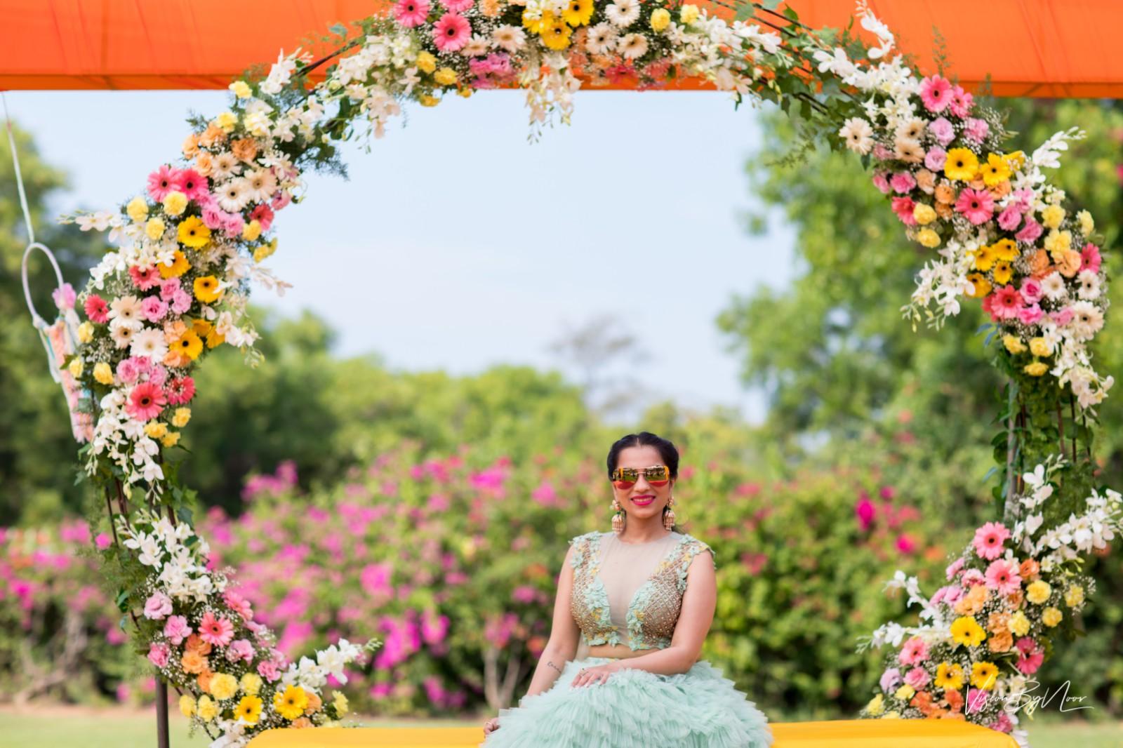 bride in pastel lehenga in front of huge floral wreath