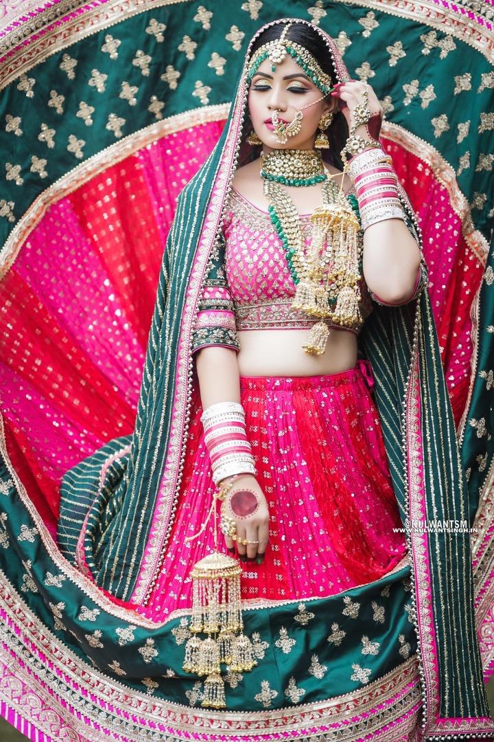 bride in pink and green bridal lehenga