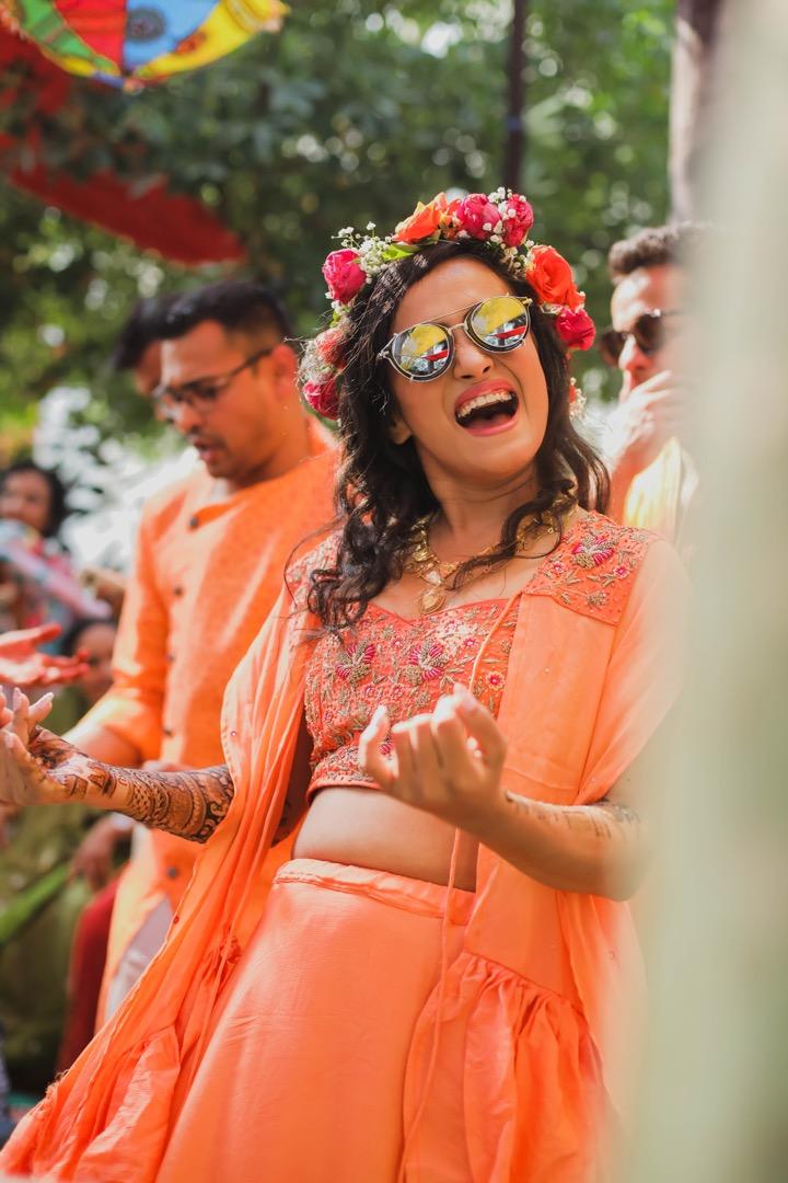 bride in orange outfit and floral tiara dancing at her mehndi