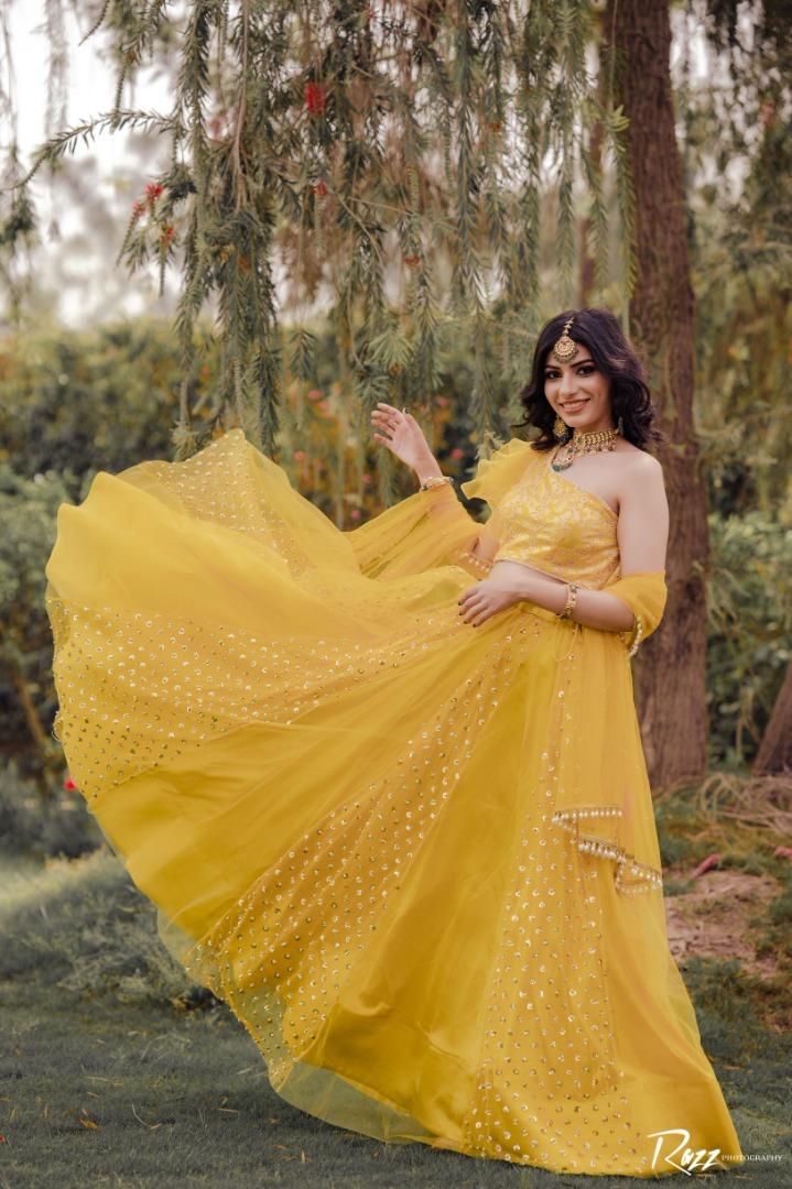 bride in a yellow one shoulder lehenga