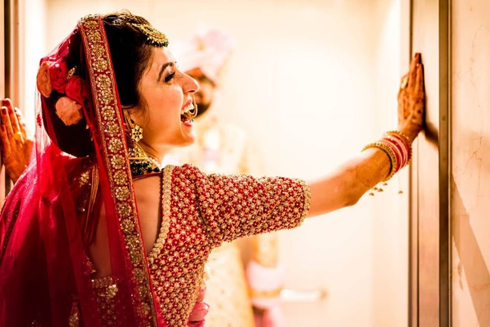 Beautiful Bride Laughing Picture in Red Lehenga and Red Bridal Makeup and Bridal Bun Hairstyle