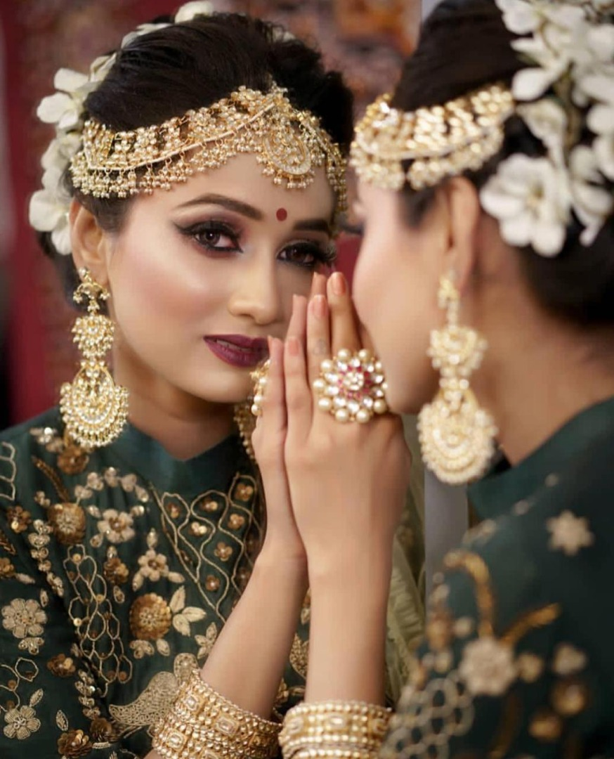 beautiful bride in green outfit with gold jewellery