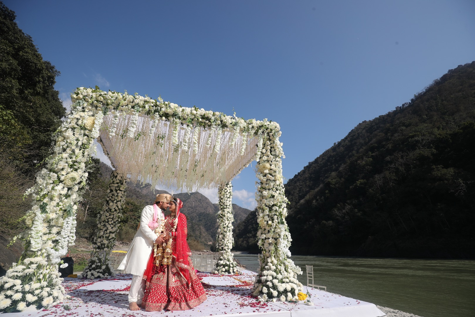 white floral mandap in front of a lake