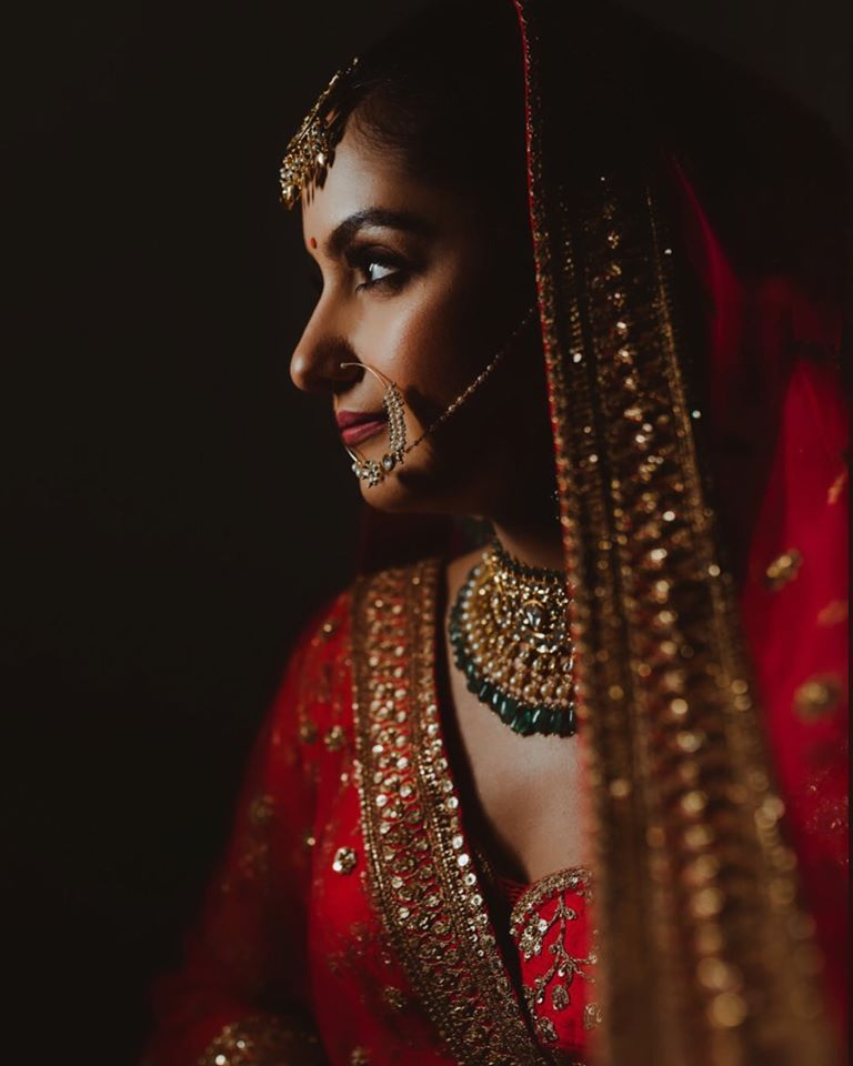 Beautiful Indian Bride in traditional red lehenga & nude bridal makeup for wedding