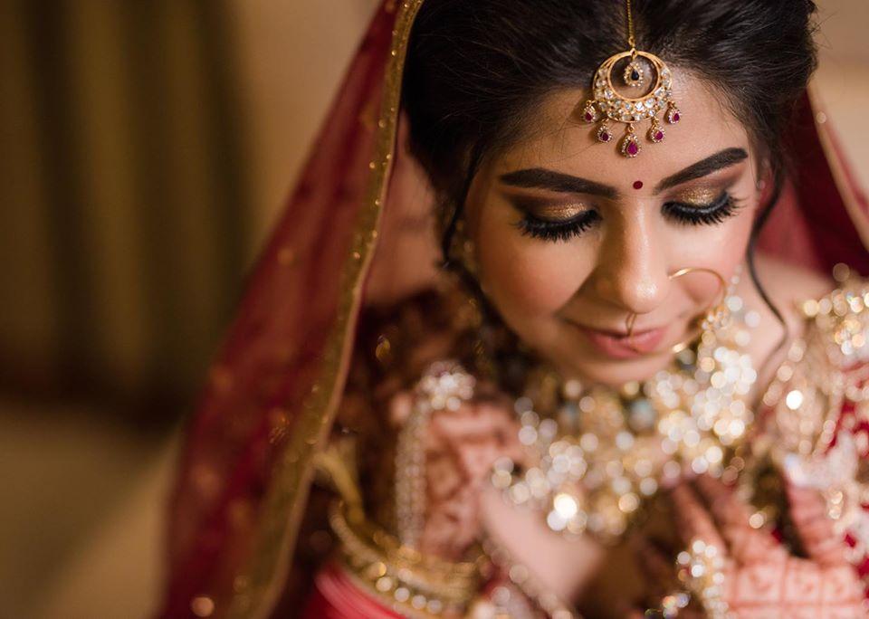 Indian Bride in glitter gold eyes, soft makeup & red wedding lehenga