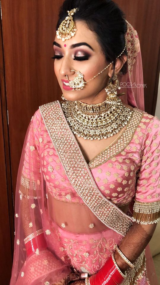 Indian bride in a pink wedding lehenga with pink eye makeup & bridal bun for her wedding
