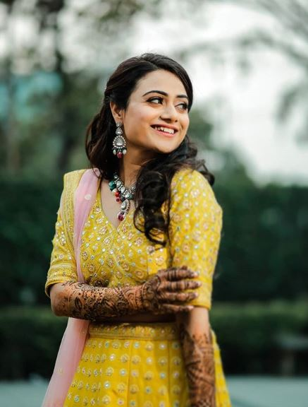 Cute Bride Smiling Solo Picture in Yellow Outfit at Mehendi Ceremony