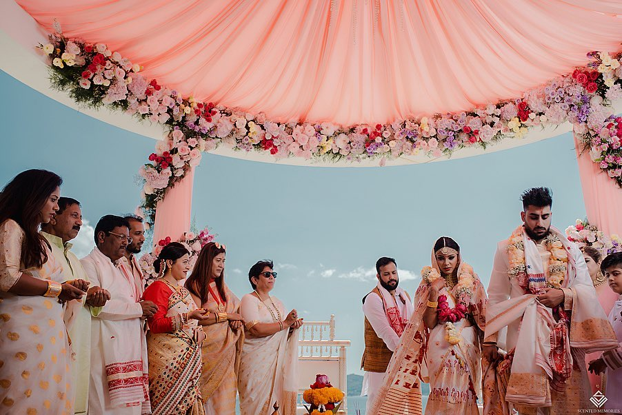 Bride and groom taking pheras in beach wedding