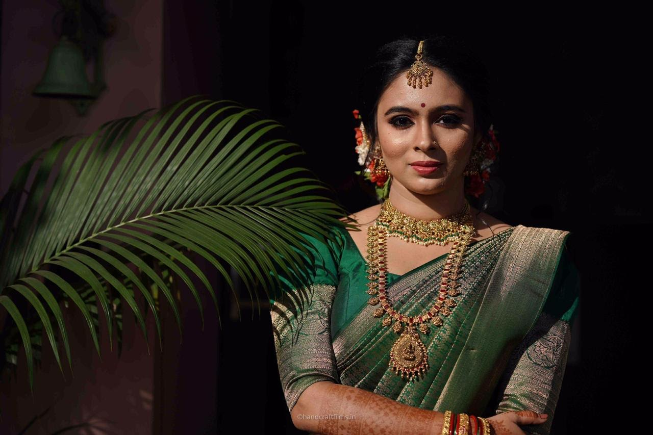 bride in green silk saree and gold temple jewelry