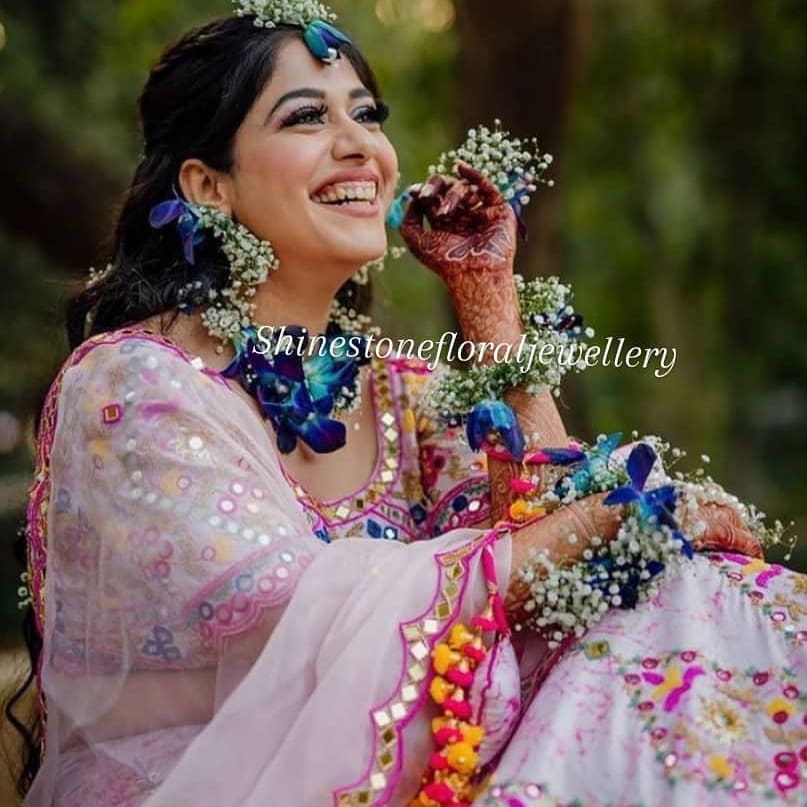 happy bride in lavender lehenga and blue floral jewelry