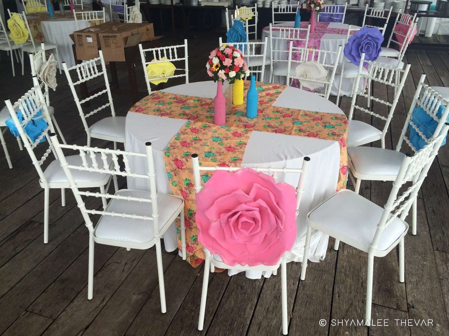 White Table & Chairs with Big Artificial Flowers & Colorful Flwer Bottle Centerpieces