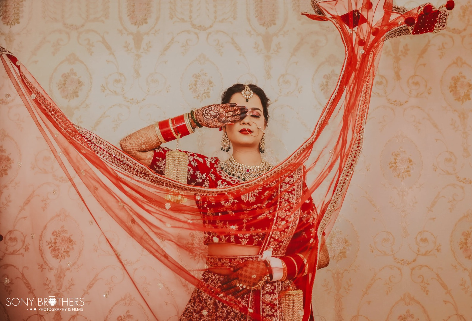 bride poses with her bridal dupatta