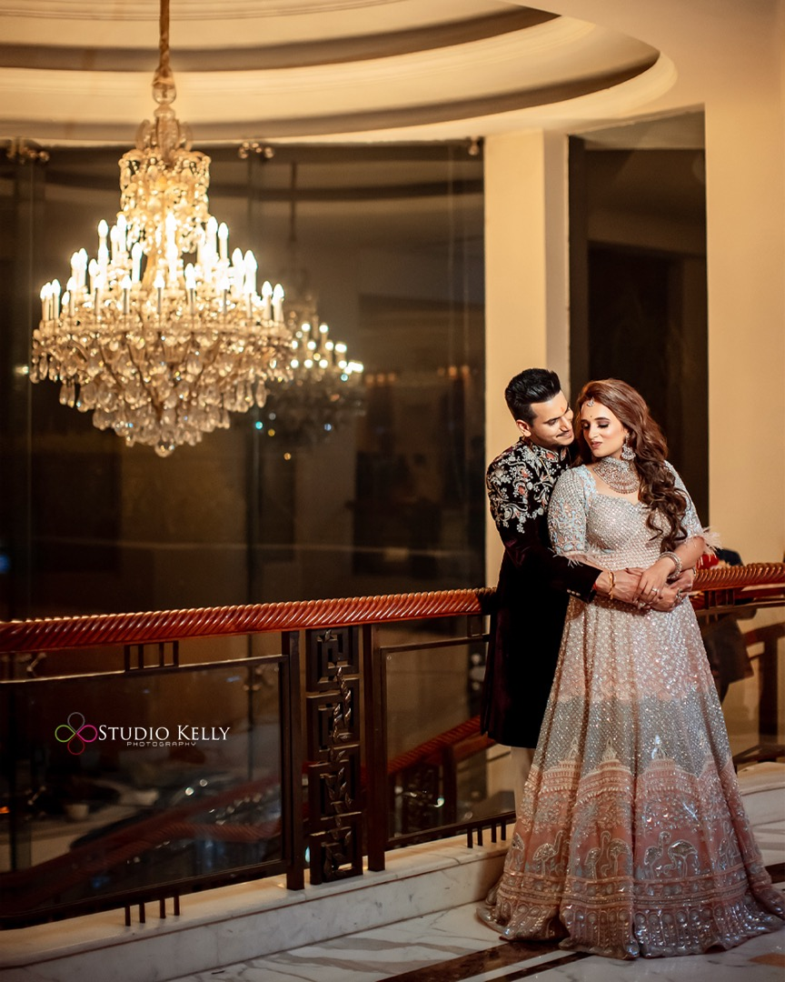 bride in a contemporary outfit poses with her groom