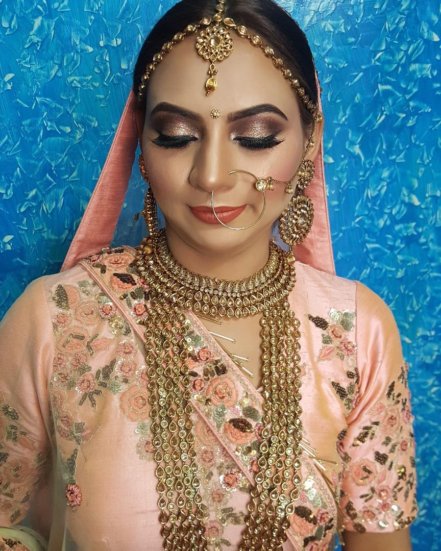 Bride in pink lehenga with beautiful golden jewelry