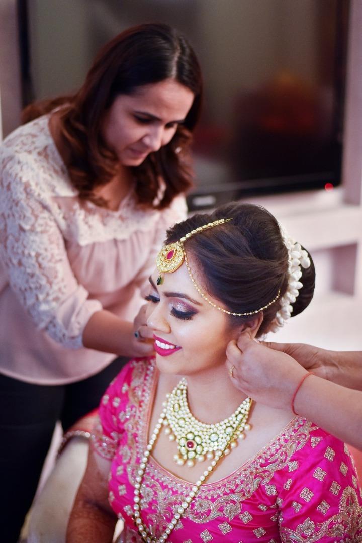 Beautiful bride getting ready in pink lehenga