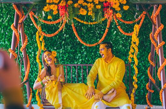 couple dressed in yellow enjoying their haldi ceremony